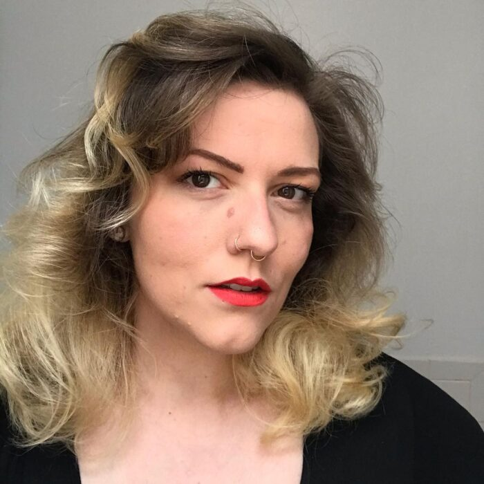 White femme-presenting person with blonde hair and red lipstick.